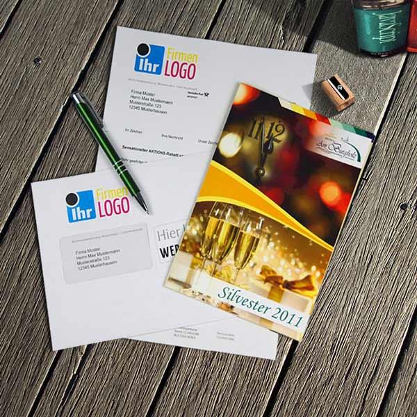 Kuvertieren: Ein adressiertes Anschreiben und ein Folder werden in eine bedruckte Kuvertierhülle kuvertiert.